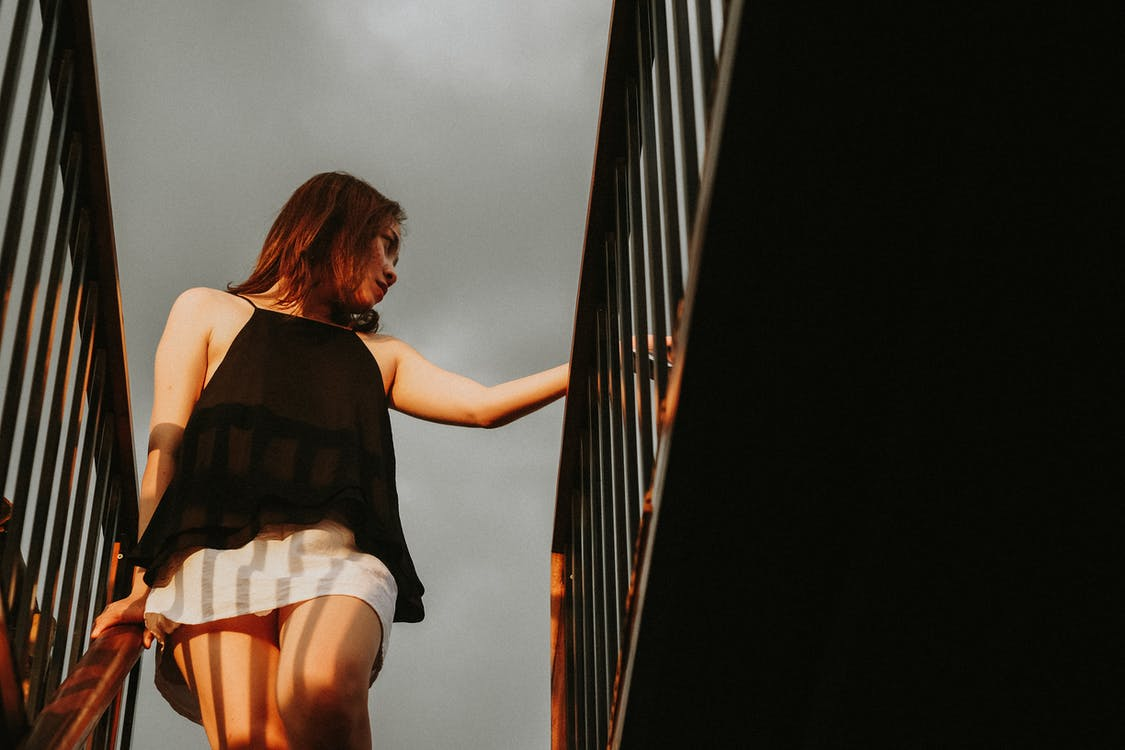 Low Angle Photo of Woman in Black Top and White Skirt Looking Away While Standing at the top of a Staircase Holding Metal Railing